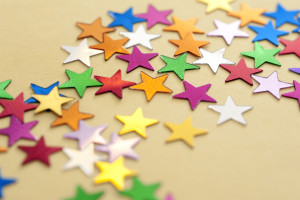 Colorful stars background with numerous, multicolored stars scattered across a festive yellow background viewed low angle with shallow dof